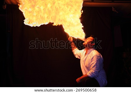 fire-eater with flame over dark background - stock photo