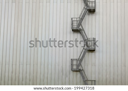Fire escape ladder on modern industrial building - stock photo