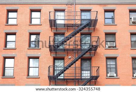 Fire escape ladders, brick building in New York, USA. - stock photo