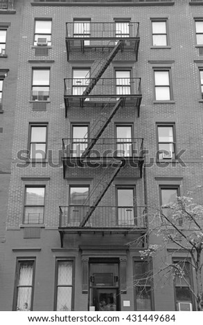 Fire escape stairway on exterior of brick walkup apartment building in New York City - stock photo