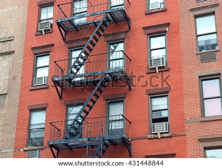 Fire escape stairway on exterior of red brick walkup apartment building in New York City - stock photo