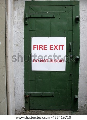 Fire exit do not block! sign on a green door - stock photo