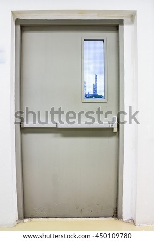Fire exit door and window view to industrial plant - stock photo