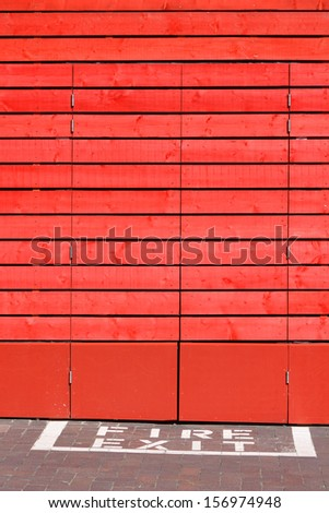 Fire exit doors in timber clad workplace building - stock photo