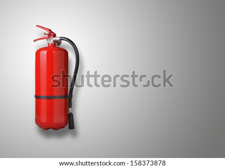 Fire extinguisher on the gray wall - stock photo