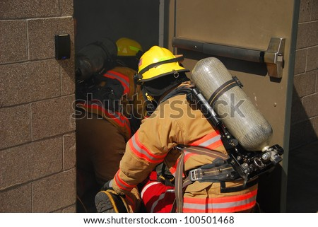 fire fighters crawling through a smoky structure with fire hose and scba - stock photo