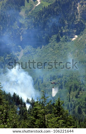 Fire fighters in a helicopter drop water on a forest fire in the wasatch mountains of Utah. - stock photo