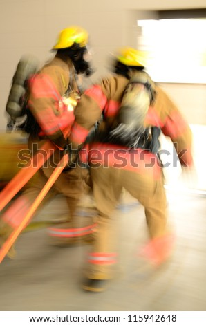 Fire fighters participating in a  trapped person training exercise - stock photo