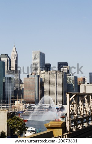 Fire fighting boat spouting water in New York City - stock photo