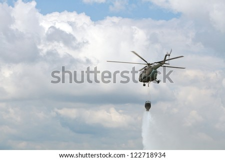 Fire fighting helicopter dropping water - stock photo