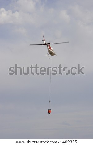 Fire fighting helicopter flying away - stock photo