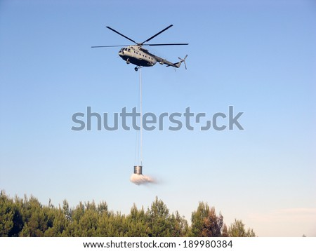 Fire fighting helicopter over burning forest  - stock photo