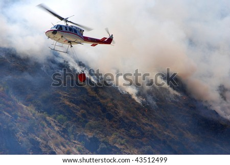 fire-fighting helicopter with a water bucket fighting a fire on a hillside - stock photo