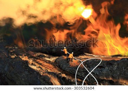Fire Fighting staff(miniature) working with wildfire. - stock photo