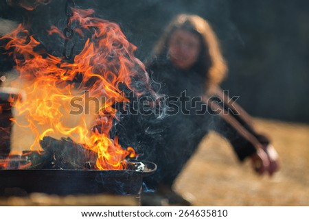 Fire flames on a grill with woman in background relaxing - stock photo