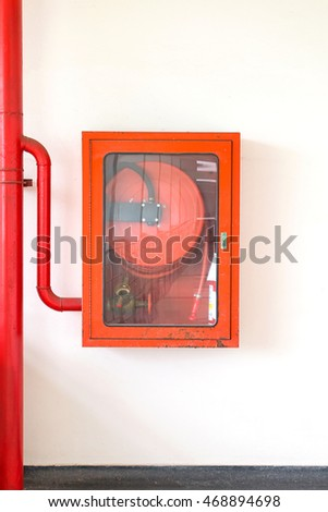 Fire hose cabinet with white wall background.