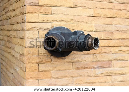 Fire hose nozzle on tone wall made with blocks - stock photo