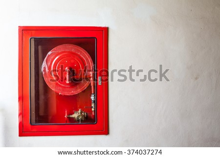 Fire hoses packed inside of red emergency box at the wall - stock photo