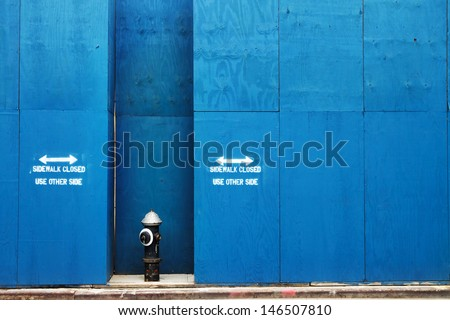 Fire Hydrant in Front of a Blue Painted Construction Wall in New York City - stock photo