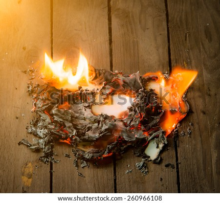 Fire paper on wooden background - stock photo