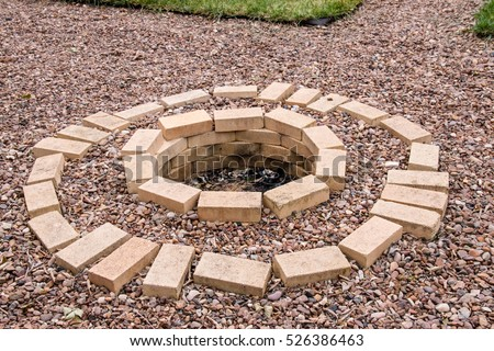 Fire pit made of the yellow aluminous bricks surrounded by pebble in the autumn garden