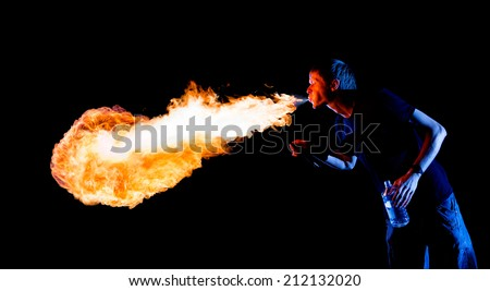 Fire show artist breathe fire in the dark - stock photo