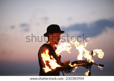 Fire showman profile on sky background - stock photo