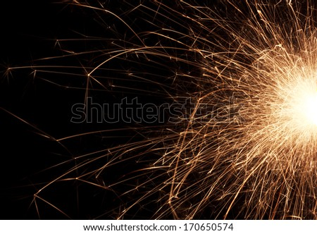 Fire spray from sparklers on black background, macro, selective focus - stock photo