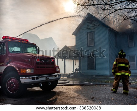 Fire Truck Spraying water on house fire  - stock photo