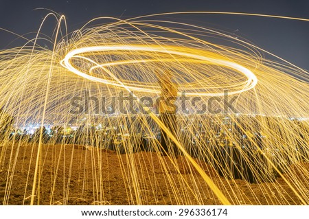 fire wire spinner on night city background - stock photo