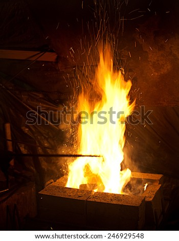 fire with flying sparks closeup on dark blacksmith workplace background - stock photo