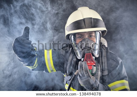 Fire woman in fire protection suit and mask - stock photo