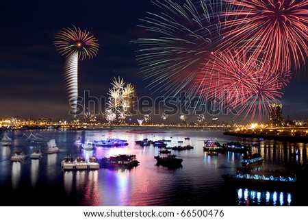 Fire works firing up into the sky with a boat on a river below them, with a reflection on the water - stock photo