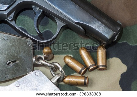 Firearm Pistol  And Hand Gun Ammunition on military camouflage background - stock photo