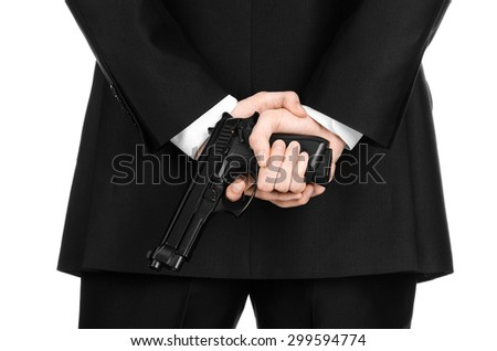 Firearms and security topic: a man in a black suit holding a gun on an isolated white background in studio - stock photo