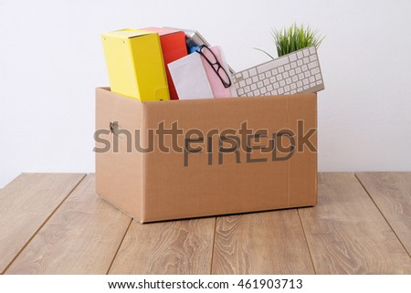 Fired businessman box with pink slip on office desk