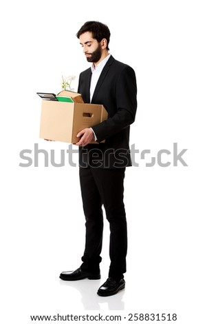 Fired businessman holding box with personal belongings. - stock photo