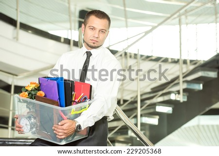Fired businessman packed his bags and leaving office. He is looking sad. - stock photo