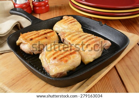Fired chicken breasts and thighs in a cast iron skillet - stock photo