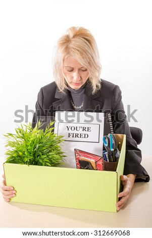 Fired corporate employee holding her belongings in a cardboard box on the desk and dismissal notification. White background, isolated.