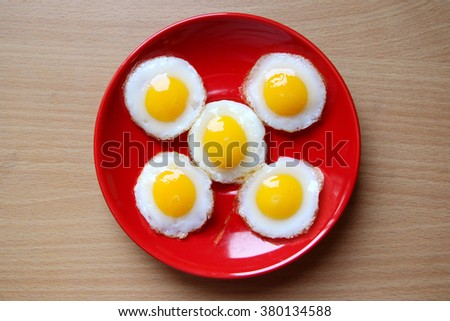 fired eggs is on Red dish. - stock photo