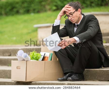 Fired frustrated man in suit sitting near office at stairs. - stock photo