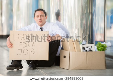 Fired frustrated man in suit sitting near office with sign. - stock photo