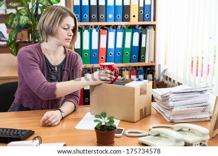 Fired office employee packing personal belongings in box - stock photo