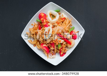 Fired papaya salad with seafood on black background - stock photo