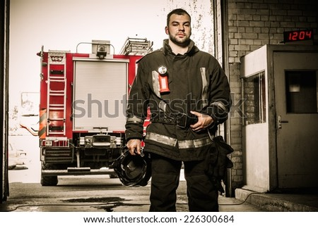Firefighter against truck in firefighting depot  - stock photo