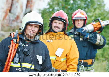 firefighter crew in uniform in front of fire engine machine and fireman team - stock photo