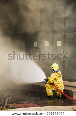 Firefighter fighting a fire of a building . Cloud of smoke surrounding - stock photo