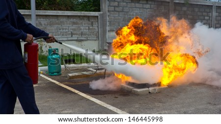 Firefighter fighting fire during training - stock photo