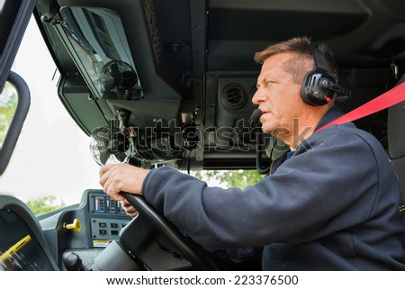 Firefighter Fire Truck Driver with Headphone on inside Commander Vehicle